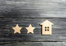 Två stjärnor och ett hus Begrepp av värderingen av ett hotell eller en restaurang Utvärdering av fastigheten, kundåsikt Hög värde royaltyfria foton