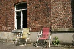 Två stolar nära ett disalated hus Royaltyfri Fotografi