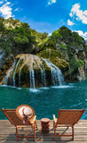 Två stolar och hatt framme av en vattenfall Royaltyfria Bilder