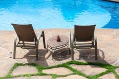 Två stolar och tabell framme av simbassängdäck i ett hotell Arkivbilder