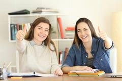 Två stolta studenter som gör en gest tummar, up hemma royaltyfri bild