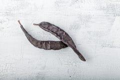 Två stora Carobs på en träbakgrund Arkivbilder