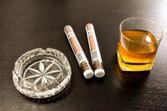 Två stora cigarrer, ett kristallaskfat och ett exponeringsglas av whisky på den svarta tabellen Bucharest Rumänien - 03 04 2019 royaltyfri fotografi