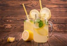 Två stora exponeringsglas av drycker för en mojito med saftiga ljusa gula citroner, ny mintkaramell, mineralvatten på en brun trä Royaltyfri Fotografi