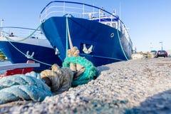 Två stora fiskebåtar binds upp med repet för skeppsdockan, marina royaltyfri fotografi