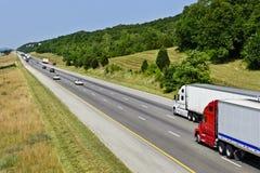 Två stora halva lastbilar på huvudvägen Fotografering för Bildbyråer