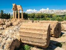 Två stora kolonner i dalen av templen av Agrigento; templet av Dioscuri i bakgrunden Arkivbild