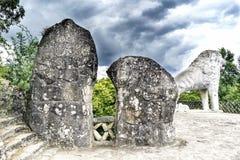 Två stora konstgjorda stenar och sikt av en lejonstaty i fonen Arkivbilder