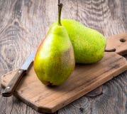 Två stora nya gröna päron och kniv på ett klipp Arkivbild