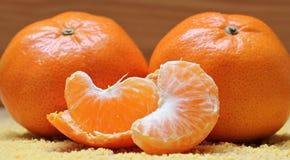 Två stora orange apelsiner, i ljusa rengjorda nya skivor för förgrund Arkivbilder