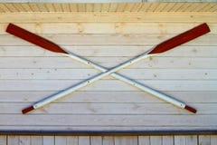 Två stora röda skovlar som hängs på den vita wood skeppväggbakgrunden fotografering för bildbyråer
