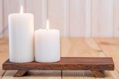 Två stora stearinljus som bränner på en träservice Royaltyfri Foto
