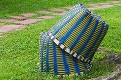 Två stora, vävde, blåa och gula plast- korgar som staplas i en stor gräsplanträdgård, ordnar till för att rymma att arbeta i träd royaltyfri bild