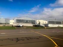 Två stora vita kraftiga snabba nivåer parkeras nära flygplanhangarerna på landningsbanan arkivfoton