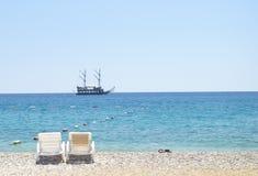 Två strandstolar mot blå himmel, azur bevattnar, gul sand och det gamla havsskeppet på en horisont semester för paraply för sky f Royaltyfri Foto