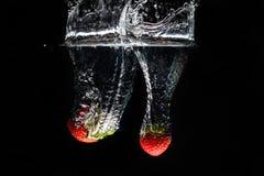 Två strawberrys som plaskar in i vatten Royaltyfri Foto