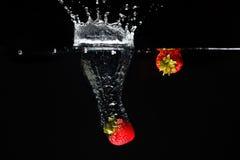 Två strawberrys som plaskar in i vatten Royaltyfri Bild