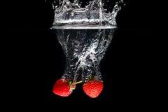 Två strawberrys som plaskar in i vatten Arkivfoto