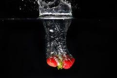 Två strawberrys som plaskar in i vatten Fotografering för Bildbyråer