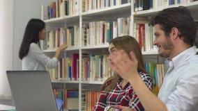 Två studenter argumenterar om något på bärbara datorn arkivfilmer