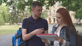 Två studenter diskuterar något i anteckningsbok på universitetsområde royaltyfria foton