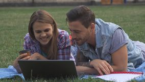 Två studenter diskuterar något på bärbara datorn på gräsmattan royaltyfria foton