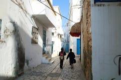 Två studenter går att skola på gatan av den gamla staden av Sousse royaltyfri fotografi