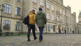 Två studenter går till ingången av universitetet arkivfilmer