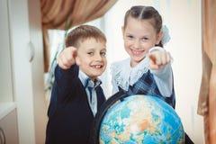 Två studenter med ett jordklot arkivbild