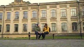 Två studenter sitter på bänken nära universitetsområde lager videofilmer