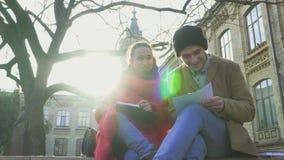 Två studenter skriver anmärkningar i anteckningsböcker som sitter på bänken parkerar in stock video