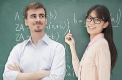 Två studenter som gör matematikformeln på den svart tavlan, Peking Royaltyfri Bild