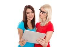 Två studenter som har gyckel med den digitala minnestavlan. Fotografering för Bildbyråer