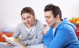 Två studenter som läser i en bok Royaltyfri Bild