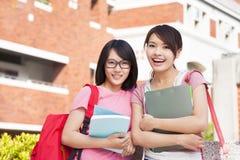 Två studenter som ler och rymmer böcker på universitetsområdet Arkivfoto