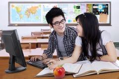 Två studenter som talar och skrattar i gruppen Arkivfoton