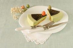 Två stycken av easter bakar ihop med för chokladganache och sötsak-material för te matchaen dekorerade ägg på den vita plattan Arkivbild