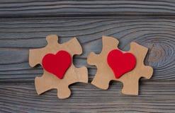 Två stycken av ett pussel med en röd hjärta, förenar in i en hel singel Arkivbild