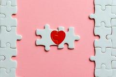 Två stycken av ett pussel med röd hjärta på rosa bakgrund Arkivfoton