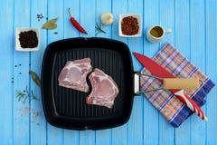 Två stycken av grisköttkött i en panna och kryddor Arkivfoton