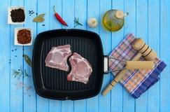 Två stycken av grisköttkött i en panna och kryddor Arkivbild