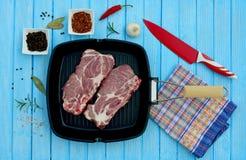 Två stycken av grisköttkött i en panna och kryddor för att laga mat Royaltyfri Bild