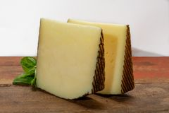 Två stycken av Manchego, quesomanchego, ost som göras i La Mancha arkivbild