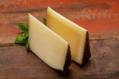 Två stycken av Manchego, quesomanchego, ost som göras i La Mancha royaltyfri foto