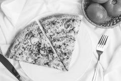 Två stycken av pizza på en vit platta, nya tomater, en gaffel och en kniv, en svartvit ram Royaltyfri Fotografi