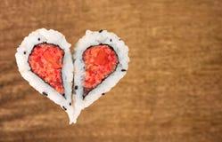 Två stycken av sushi som bildar hjärtaformen arkivfoton
