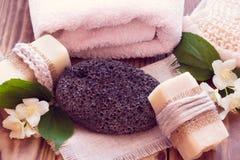 Två stycken av torr tvål med en jasmin, handduken, polermedel och en bast Royaltyfria Foton