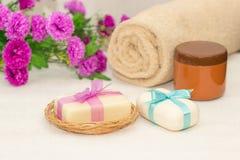 Två stycken av tvål med en korg med pilbågar, blommor, handduk a Arkivbild