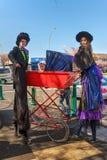 Två styltafotgängare och en mycket högväxt barnvagn arkivfoton