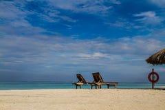 Två sunbeds i sanden på den tropiska stranden Royaltyfri Fotografi